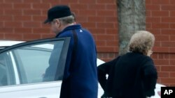FILE - John Hinckley, left, gets into his mother's car in front of a recreation center during a sanctioned visit with her, in Williamsburg, Virginia, March 19, 2015.