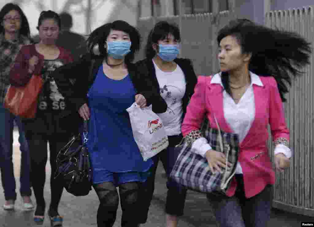 2013年5月6日在北京,戴口罩的婦女過馬路。美國大使館把監測到的北京空氣質量歸類為危險。