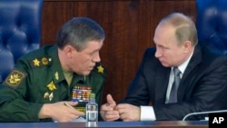 FILE - Russian President Vladimir Putin, right, speaks with the Chief of the General Staff of the Russian Armed Forces Valery Gerasimov at a meeting with top military officials in Moscow, Russia, Dec. 11, 2015. Putin is said to be considering the deployment of ground troops in Syria.