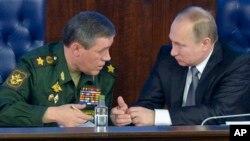 Tổng thống Nga Vladimir Putin (phải) nói chuyện với Bộ trưởng Bộ Tổng tham mưu các lực lượng vũ trang Nga Valery Gerasimov tại một cuộc họp với các quan chức quân sự hàng đầu ở Moscow, Nga, ngày 11/12/2015.