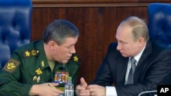 2015年12月11日,俄羅斯總統普京與俄軍總參謀長格拉西莫夫上將交談。