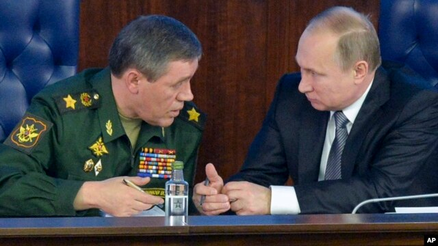 FILE - Russian President Vladimir Putin (r) speaks with the Chief of the General Staff of the Russian Armed Forces, Valery Gerasimov, at a meeting with top military officials in the National Defense Control Center in Moscow, Dec. 11, 2015.