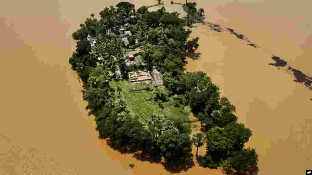 An aerial view shows houses surrounded by monsoon flooding in Orissa state, India.