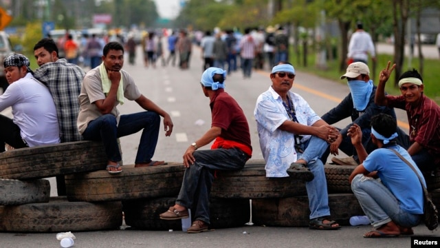 FILE - Rubber farmers sit on tires as they block a road during a protest in Surat Thani, Sept. 3, 2013.