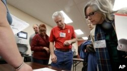 Observers look over test results as a statewide presidential election recount begins Dec. 1, 2016, in Milwaukee.