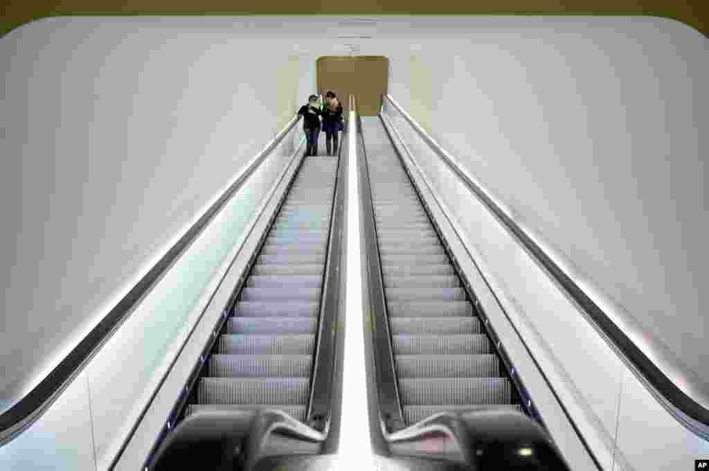 "Two visitors take an escalator after attending a press preview of the exhibit ""The Oasis of Matisse"" at Stedelijk Museum in Amsterdam, Netherlands."