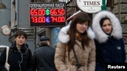 The Russian ruble fell sharply on opening on Monday, following a weekend of violence in eastern Ukraine and threats of further Western sanctions against Russia. People walk past a board showing currency exchange rates in Moscow, Jan. 26, 2015.