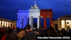 Người dân đứng trước cổng Brandenburg ở Đức được nhuộm màu quốc kỳ Pháp để tưởng nhớ tới các nạn nhân các vụ tấn công ở Paris, 14/11/2015.