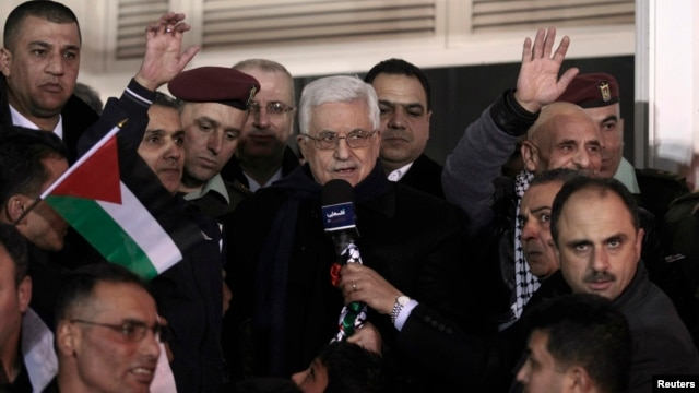 FILE - Palestinian President Mahmoud Abbas (C) speaks in the West Bank city of Ramallah, Dec. 31, 2013.