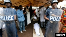 FILE - Security forces stand guard near the bodies of protesters, killed during a rally, in Conakry, Guinea, Oct.2, 2009.