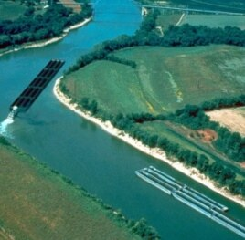 A long barge, full of coal and pushed by a tug, makes the tricky turn around one of the bends in the Cumberland River in Kentucky.