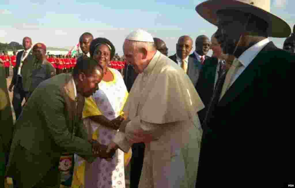 Papa Francis akisalimiwa kwa unyenyekevu na mmoja wa waumini waliofika kumlaki baada ya kuwasili Uganda.