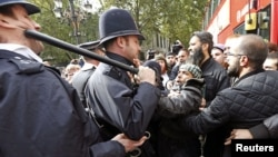 Police officers scuffle with demonstrators during a protest in support of Islamist cleric Abu Hamza al-Masri, during his appeal against extradition to the U.S., outside the High Court in London, October 5, 2012.