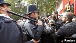 5일 영국 고등법원 밖에서 아부 함자의 미국 인도 판결에 항의하는 시위대를 제압하는 경찰관.