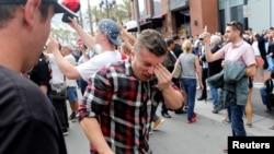 共和党总统候选人川普2016年5月27日在加州圣迭戈一次竞选集会场外的示威活动中,一名男子在被喷辣椒喷雾后捂着自己的脸。