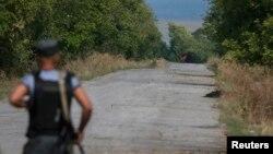 Lá cờ đỏ gắn trên chiếc xe tăng của phe ly khai thân Nga đậu gần một chốt kiểm soát của vệ binh Ukraine trong thị trấn Slavyanoserbsk, trong vùng Luhansk, 10/9/14