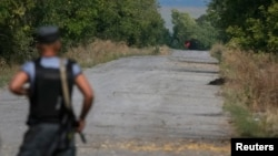 A red flag attached to a pro-Russian separatist tank is seen near a checkpoint of the Ukrainian national guard near the town of Slovyanoserbsk, Luhansk region, Sept.10, 2014.