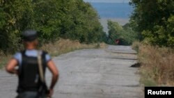 FILE - A red flag attached to a pro-Russian separatist tank is seen near a checkpoint near the town of Slovyanoserbsk, Luhansk region, eastern Ukraine, Sept.10, 2014..