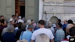 Những khách hàng đầu tiên, hầu hết là những người đã về hưu, xếp hàng chờ đợi trước một chi nhánh của Ngân hàng Quốc gia Hy Lạp tại Athens, Thứ Hai, ngày 20 tháng 7, 2015.