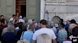 20일 다시 문을 연 그리스 아테네의 은행 문 앞에서 사람들이 줄을 서서 들어가고 있다.
