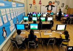 FILE - Elementary students work on computers in Los Angeles, May 15, 2012.