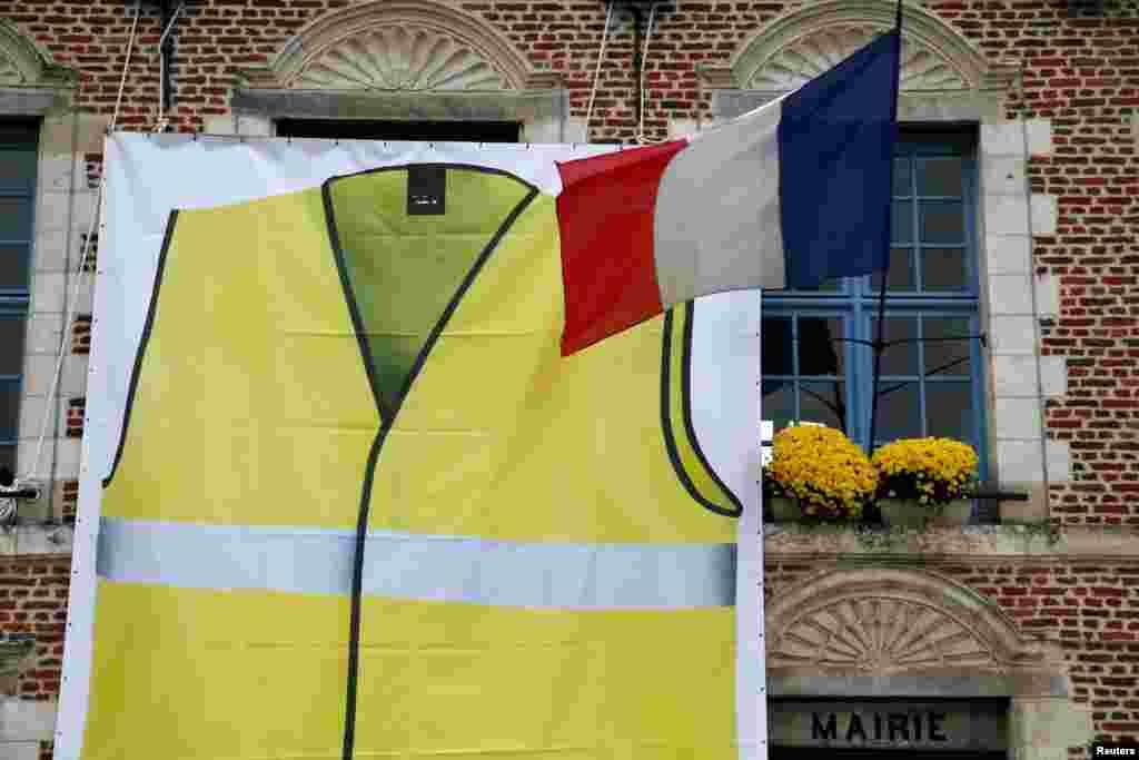 نصب یک جلیقه زرد رنگ بزرگ بر روی یک ساختمان شهرداری در شمال فرانسه ، نماد اعتراض رانندگان فرانسوی نسبت به افزایش قیمت سوخت در آن کشور.