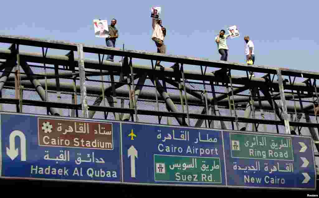 Members of the Muslim Brotherhood and supporters of ousted Egyptian President Mohamed Morsi atop a bridge during a rally around Rabaa Adawiya Square, Cairo July 26, 2013.