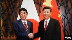2017年11月11日习近平在越南与安倍会谈前笑容握手(日本首相官邸档案图片)