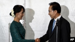 South Korean President Lee Myung-bak, right, shakes hands with Burma opposition leader Aung San Suu Kyi in Rangoon, May 15, 2012.