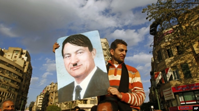 A protester holds a placard depicting Egyptian President Hosni Mubarak as Adolf Hitler in Cairo's Tahrir Square, January 31, 2011