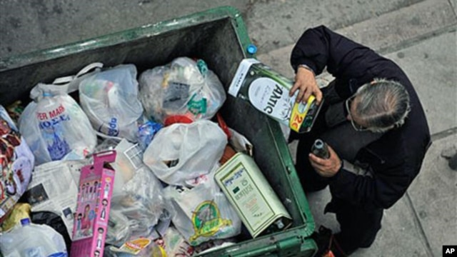 A man empties out the remains of an olive oil container from a trash bin in the northern Greek port city of Thessaloniki, Greece, January 4, 2011