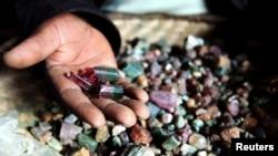 Un vendeur des minérais congolais montre des pierres précieuses dans une hutte de boue au Numbi dans l'est du Congo.