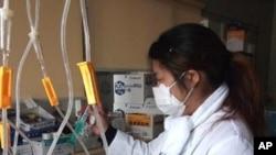 Nurse Tomimo Goto prepares medicine in the darkened ward of the Sen-en Hospital in Tagajo, Japan