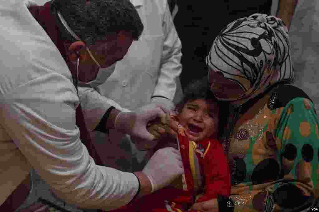 Para dokter memeriksa kesehatan seorang anak Suriah di klinik dalam kamp pengungsi. Di antara masalah yang paling umum adalah penyakit pernafasan seperti bronkhitis. (VOA/John Owens)