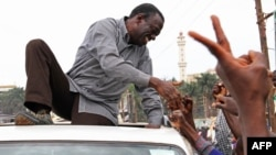 Ugandan opposition party leader Kizza Besigye shakes hands with supporters before being arrested on September 4, 2012 in Kampala, Uganda.
