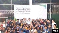 Tujuh puluh satu warga Jawa Barat disambut Gubernur Jabar Ridwan Kamil di Bandung, usai dipulangkan usai kerusuhan di Wamena, Papua. (VOA/Rio Tuasikal)