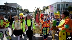 FILE - Clowns carry a statue of the Virgin of Guadalupe, as they arrive at the Basilica of Our Lady of Guadalupe in Mexico City, Dec. 14, 2015.