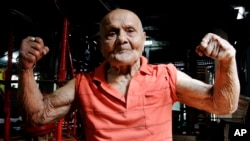 FILE- In this March 16, 2012, photo, Indian bodybuilder Manohar Aich flexes his muscles as he poses for a photograph at a gymnasium in Kolkata, India.