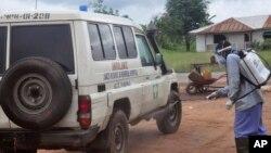 Petugas kesehatan menyemprotkan disinfektan pada ambulans yang digunakan untuk membawa dua orang yang diduga terjangkit virus Ebola di pinggiran kota Monrovia, Liberia (1/7). (AP/Abbas Dulleh)