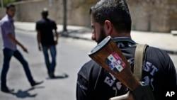 """Un soldado del ejército de Siria custodia un puesto de control con su Ak-47 con una calcomanía del presidente Bashar al-Assad que dice """"Siria está bien""""."""