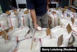 Seorang pelanggan mengecek kualitas beras saat berbelanja di pasar beras Cipinang di Jakarta, 22 Januari 2016. (Foto: Reuters/Garry Lotulung)