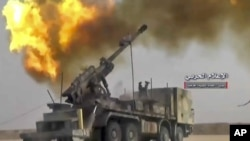 FILE - Photo taken from video provided by the government-controlled Syrian Central Military Media shows firing on militants' positions on the Iraq-Syria border, Nov 8, 2017. The Britain-based Syrian Observatory for Human Rights said Islamic State militants have withdrawn from their last stronghold following a government offensive.