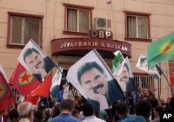 FILE - People hold posters of jailed PKK leader Abdullah Ocalan and PKK flags as they gather outside the headquarters of pro-Kurdish Democratic Regions Party, DBP, on the17th anniversary of Ocalan's expulsion from Syria, in Diyarbakir, Turkey, Oct. 9, 2015.