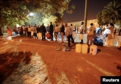 In Cape Town, South Africa, Jan. 25 2018, people wait their turn to take water from a spring in the Newlands suburb as fears over the city's water crisis grow.