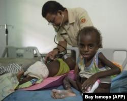 Anggota Satgas TNI memeriksa anak di rumah sakit setempat di Agats, Ibu Kota Kabupaten Asmat pada 26 Januari 2018.(Foto: AFP/Bay Ismoyo)