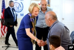 FILE - The U.S. ambassador to Jordan, Alice Wells, shakes hands with Syrian refugees ahead of their departure to the United States, Aug. 28, 2016.