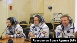 In this handout photo released by Roscosmos, actress Yulia Peresild, left, film director Klim Shipenko, right, and cosmonaut Anton Shkaplerov speak with their relatives through a safety glass prior the launch at the Baikonur Cosmodrome, Kazakhstan, Tuesday, Oct. 5, 2021.