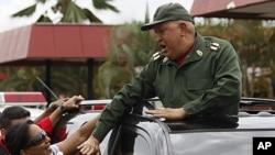 Venezuela's President Hugo Chavez greets supporters as he passes through the town of La Fria, on his way to La Grita, Venezuela, October 20, 2011.