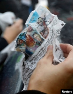 FILE - A journalist holds an anti-Pyongyang leaflet.