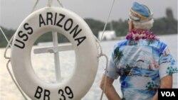 Un sobreviviente del ataque de 1941 en Pearl Harbor, junto a una replica de un salvavidas del USS Arizona.